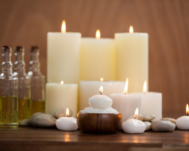 Candles with massage oil bottles and sea salt in wooden bowl on table