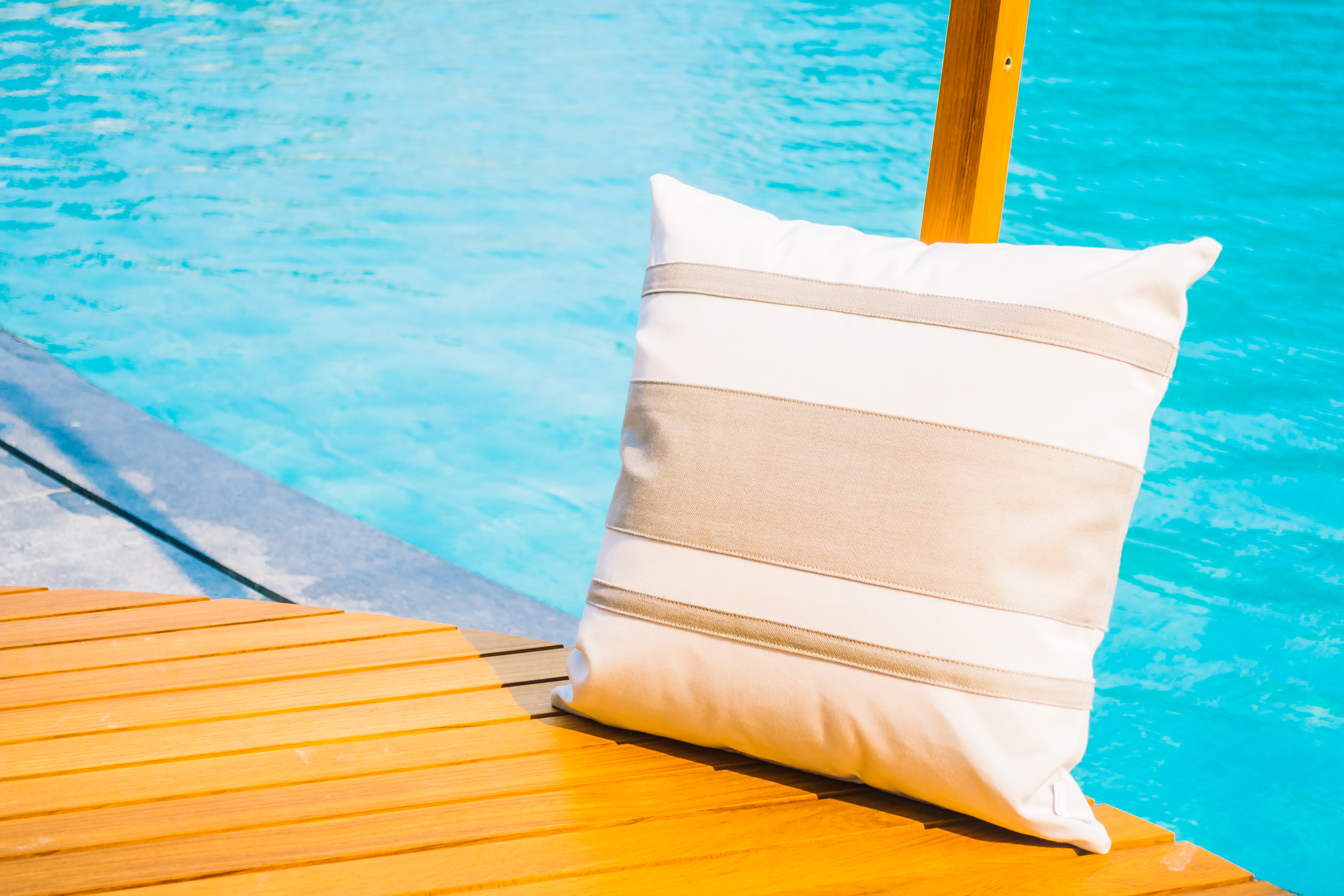Selective focus point at pillow on deck around swimming pool in hotel resort - Vintage Light Filter
